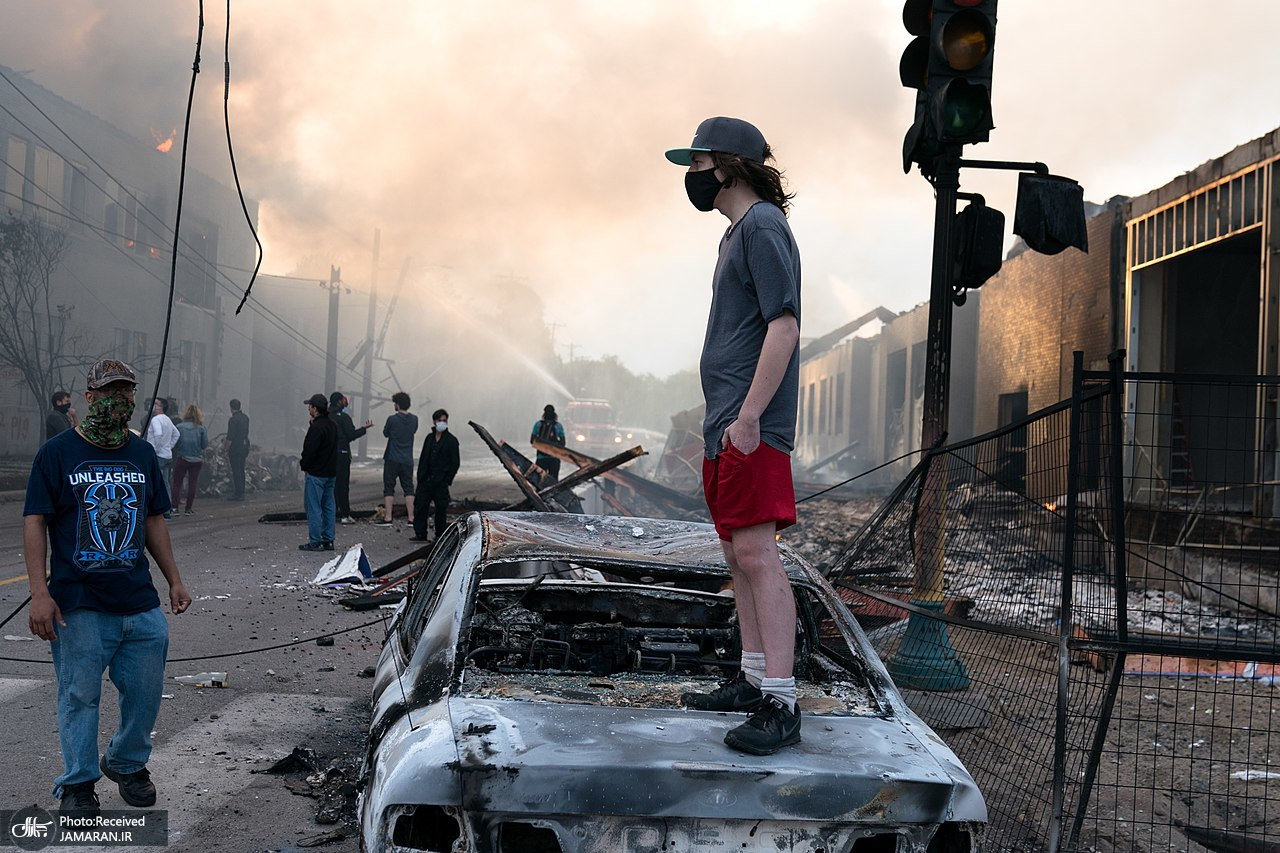 1280px-A_man_stands_on_a_burned_out_car_on_Thursday_morning_as_fires_burn_behind_him_in_the_Lake_St_area_of_Minneapolis__Minnesota_(49945886467)